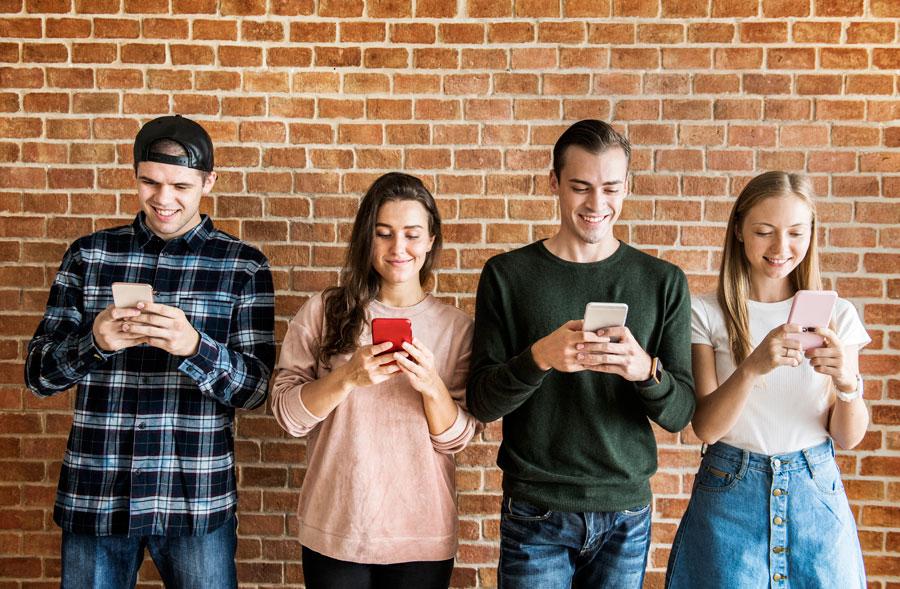 Joves mirant els seus mòbils, on es poden descarregar l'app Closely.